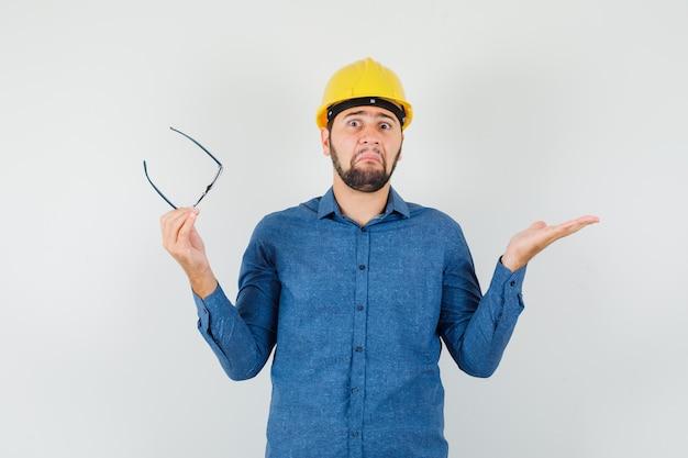 シャツを着た若い男性、眼鏡をかけたヘルメット、無力なジェスチャーを示し、混乱しているように見える、正面図。