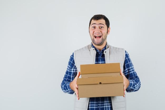 Молодой мужчина в рубашке, куртке, холдинг коробки и рад, вид спереди.