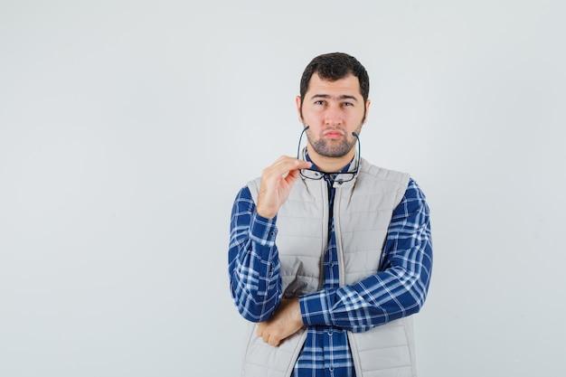 셔츠에 젊은 남성, 생각하고 사려 깊은 찾고있는 동안 안경을 들고 재킷