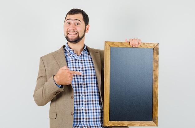셔츠, 칠판에 가리키는 재킷과 유쾌한, 전면보기에 젊은 남성. 무료 사진