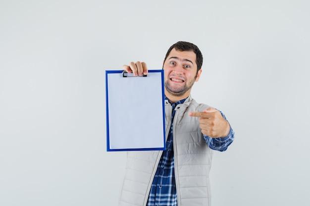 シャツを着た若い男性、空白のクリップボードを指し、満足そうに見えるジャケット、正面図。