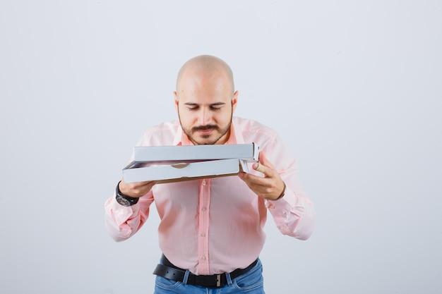 셔츠를 입은 젊은 남성, 청바지 냄새가 나는 피자 상자를 열고 기뻐하며 정면을 바라보고 있습니다.