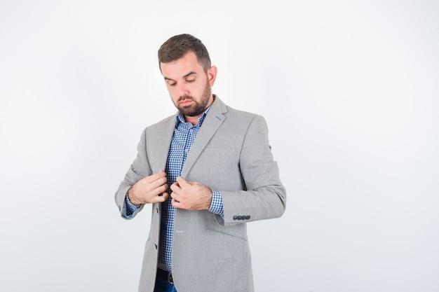 シャツ、ジーンズ、スーツのジャケットを着た若い男性がポーズをとって真剣に見ながら襟を保持し、正面図。