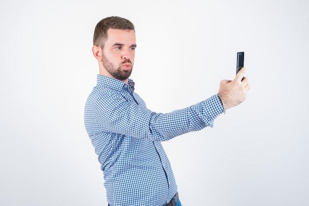 シャツを着た若い男性、唇をふくれっ面しながらセルフィーを撮り、キュートに見えるジーンズ、正面図。