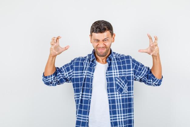 積極的な方法で手を保ち、イライラして見えるシャツを着た若い男性、正面図。