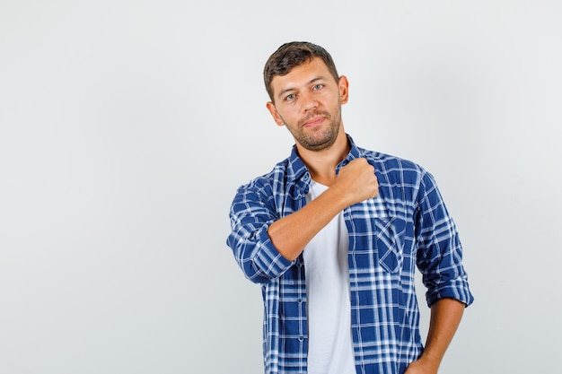 腕のくいしばられた握りこぶしを見せて、自信を持って、正面図を見てポーズをとるシャツの若い男性。
