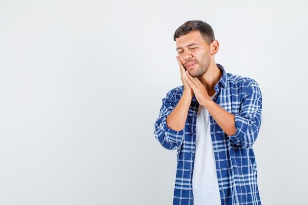 歯痛に苦しんでいるシャツの若い男性、正面図。