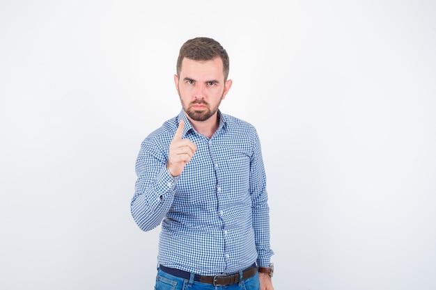 指で脅し、真剣に見えるシャツを着た若い男性、正面図。