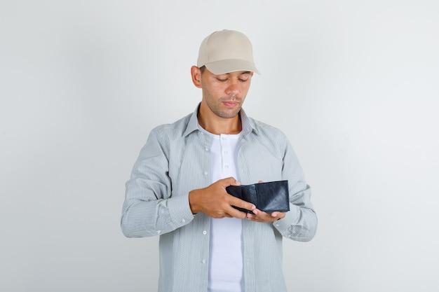 Молодой мужчина в рубашке с кепкой смотрит в открытый кошелек и смотрит осторожно