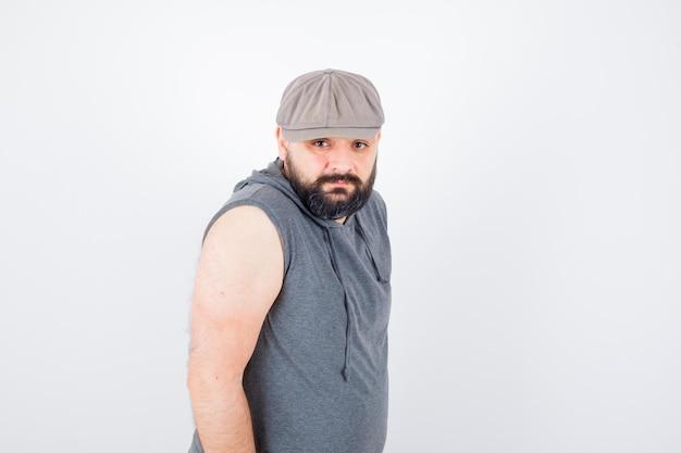 Молодой мужчина в балахоне без рукавов, кепке, смотрящей в камеру и скучающей, вид спереди.