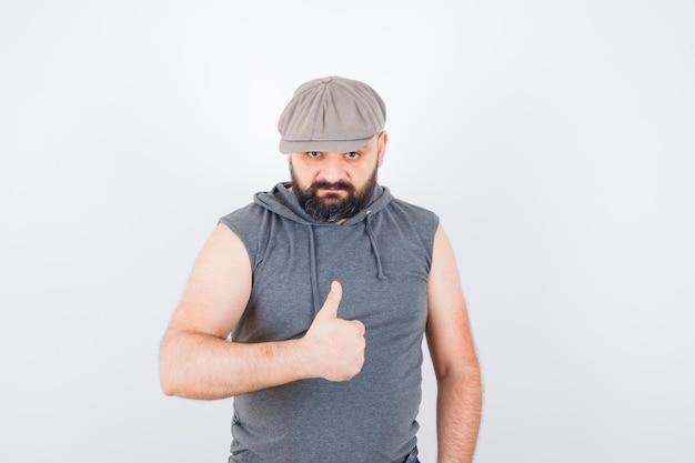 Молодой мужчина в толстовке без рукавов, кепке показывает палец вверх и выглядит уверенно, вид спереди.