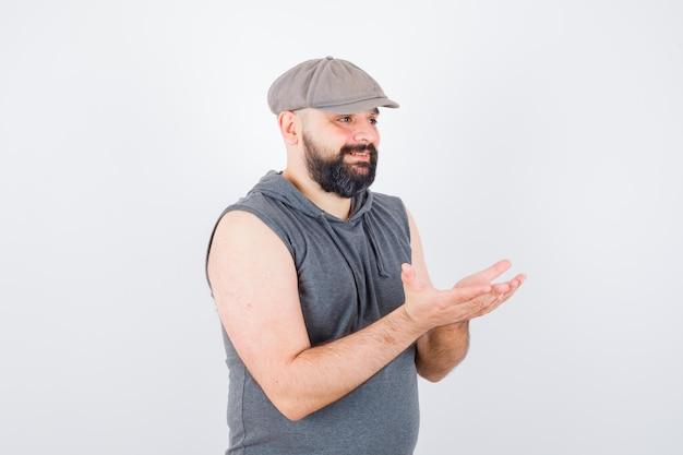 민소매 후드티를 입은 젊은 남성, 모자를 움켜쥐고 손을 뻗고 행복해 보이는 앞모습.