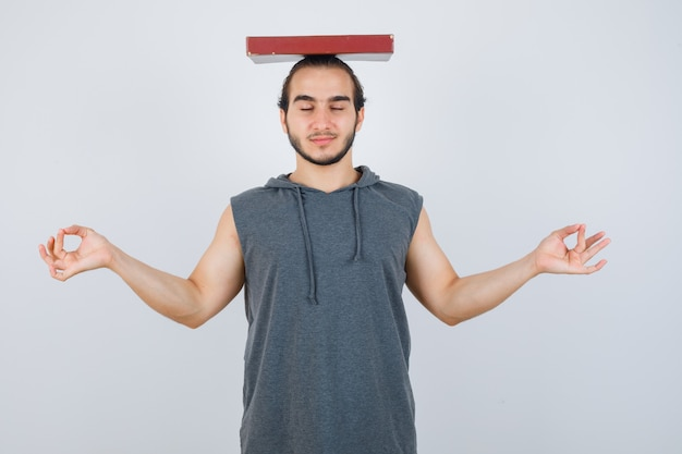 Молодой мужчина в толстовке с капюшоном без рукавов, держа книгу на голове, показывая жест медитации и выглядя мирно, вид спереди.
