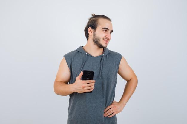 腰に手を保ち、ハンサムに見える間、携帯電話を保持しているノースリーブのパーカーの若い男性、正面図。