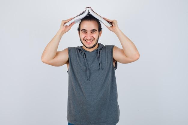 Молодой мужчина в толстовке с капюшоном без рукавов держит открытую книгу на голове как крышу дома и выглядит смешно, вид спереди.