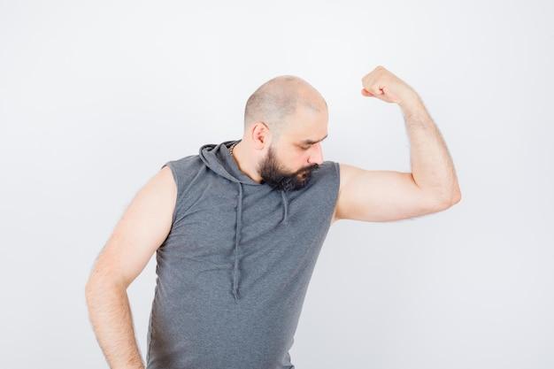 Молодой мужчина в толстовке с капюшоном без рукавов показывает мышцы рук и выглядит уверенно, вид спереди.