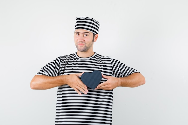 스트라이프 티셔츠, 모자 미니 선물 상자, 전면보기를 들고있는 젊은 남성.