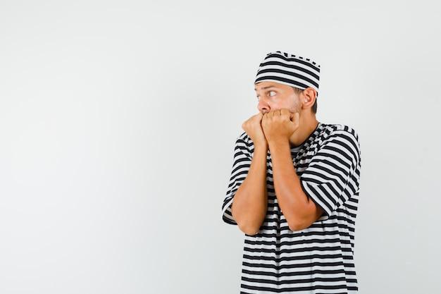 Молодой мужчина в полосатой футболке, эмоционально кусает кулаки и выглядит напуганным