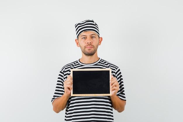 칠판을 들고 진정 찾고 스트라이프 티셔츠 모자에 젊은 남성