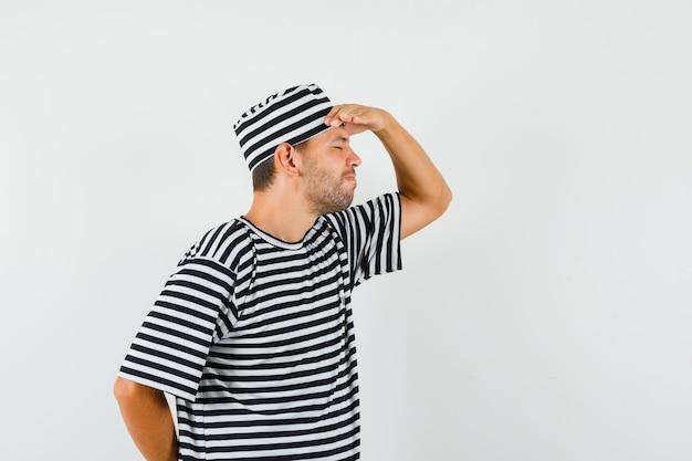 Молодой мужчина в полосатой шляпе-футболке держит руку над глазами и выглядит усталым