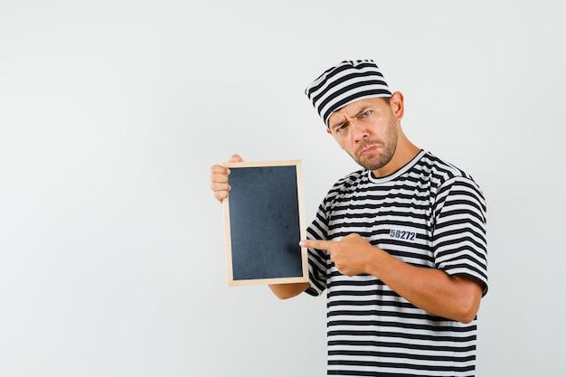 칠판을 가리키고 우울한 찾고 스트라이프 티셔츠 모자에 젊은 남성