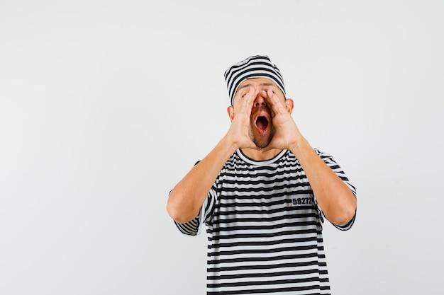 열린 입 근처 손으로 비밀을 말하는 스트라이프 티셔츠 모자에 젊은 남성