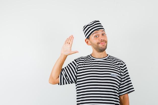 Молодой мужчина в полосатой футболке, машет рукой для приветствия и выглядит весело