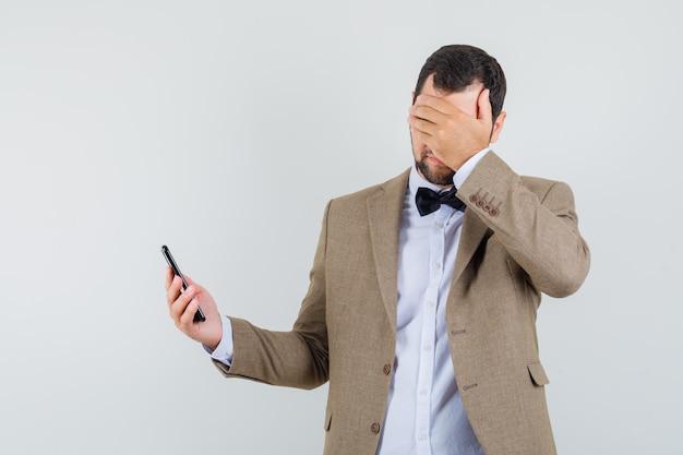 Молодой мужчина в костюме держит мобильный телефон и смотрит забывчивый, вид спереди.