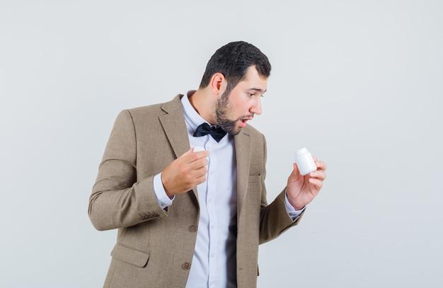 Молодой мужчина в костюме смотрит в бутылку с таблетками и удивленно смотрит, вид спереди