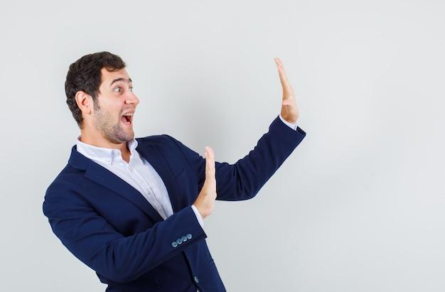 スーツを着た若い男性が、自分を押して怖がって、正面から見て停止ジェスチャーを示しています。