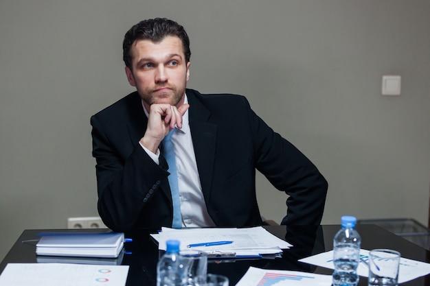 テーブルに座って目をそらしているスーツを着た若い男性。