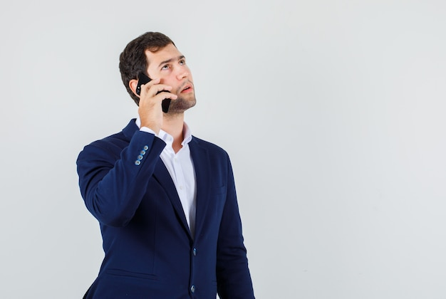 Молодой мужчина в костюме думает во время разговора на смартфоне и выглядит серьезным, вид спереди.