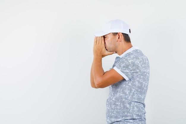 祈りのジェスチャーで手をつないで、希望に満ちたtシャツと帽子の若い男性