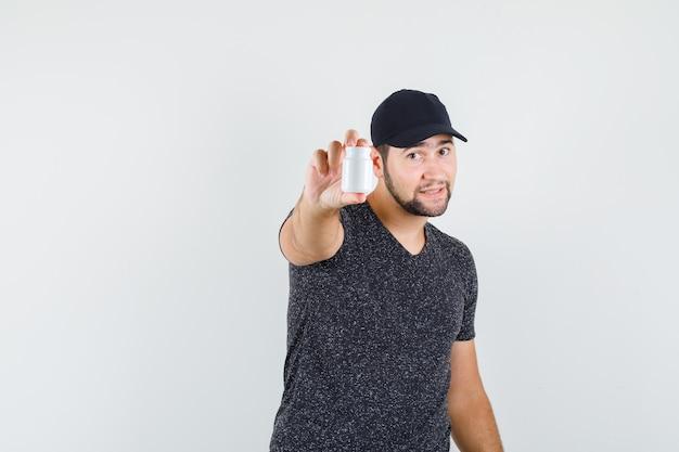 Молодой мужчина в футболке и кепке держит пластиковую бутылку с таблетками