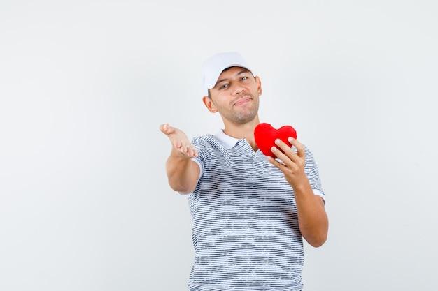 Молодой мужчина в футболке и кепке держит красное сердце, протягивает руку и выглядит весело