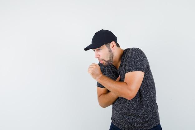 Молодой мужчина в футболке и кепке, джинсах страдает от боли в сердце и выглядит больным