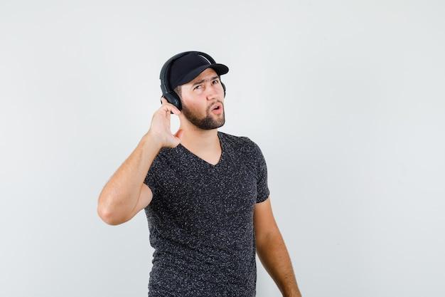 Молодой мужчина в футболке и кепке слушает музыку в наушниках и выглядит задумчиво