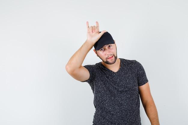 Tシャツと帽子をかぶった若い男性が頭に「愛してる」ジェスチャー