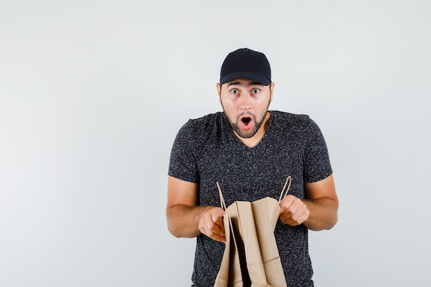 T- 셔츠와 모자 종이 가방을 열고 호기심을 찾고있는 젊은 남성