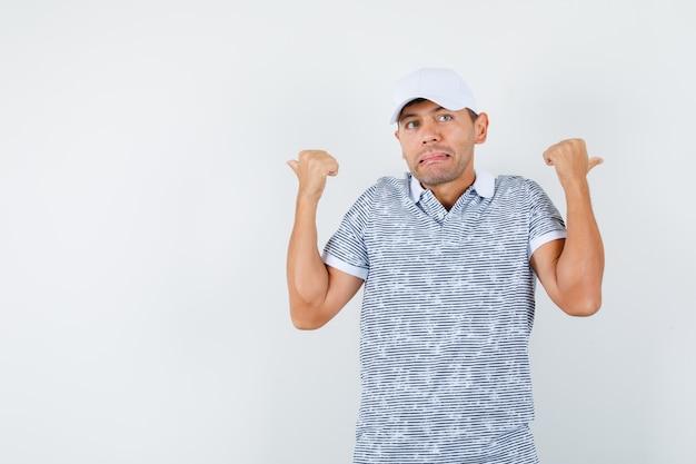 Молодой мужчина в футболке и кепке указывает большими пальцами назад и выглядит смущенным