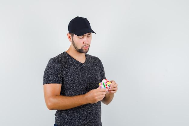 Молодой мужчина в футболке и кепке пытается собрать кубик рубика и задумчиво выглядит