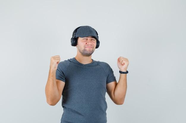 Tシャツを着た若い男性、ヘッドフォンで音楽を楽しんで、嬉しそうに見えるキャップ、正面図。