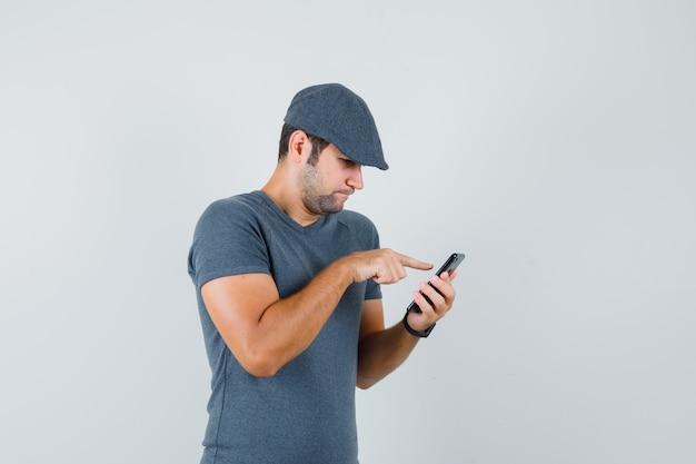 携帯電話を使用して忙しそうに見えるtシャツのキャップの若い男性