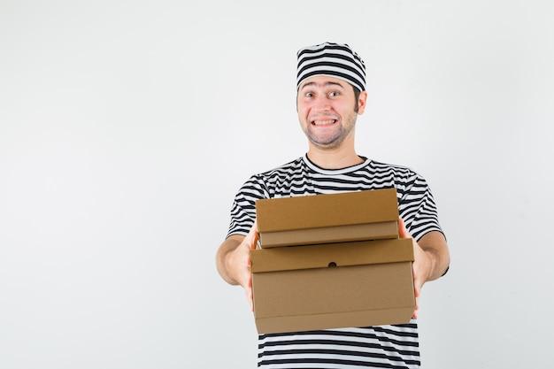 Tシャツを着た若い男性、段ボール箱を配達し、陽気に見える帽子、正面図。