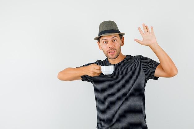 Молодой мужчина в шляпе-футболке держит чашку напитка, машет рукой и выглядит весело