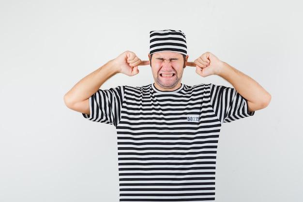 T- 셔츠, 손가락으로 귀를 연결 하 고 짜증이, 전면보기를 찾고 모자에 젊은 남성.