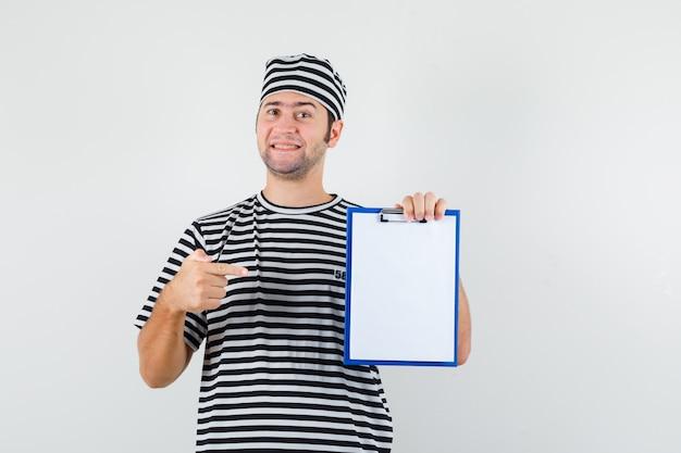 Tシャツを着た若い男性、クリップボードを指して陽気に見える帽子、正面図。
