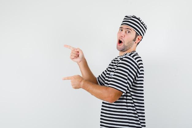 Tシャツを着た若い男性、左側を指して自信を持って見える帽子。