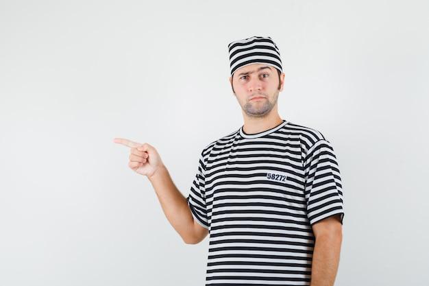 Tシャツを着た若い男性、左側を指して躊躇している帽子、正面図。