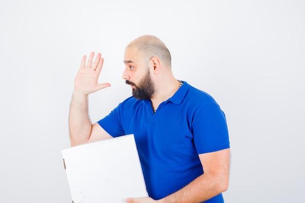 티셔츠를 입은 젊은 남성이 닫힌 피자 상자를 들고 손을 흔들며 놀란 표정을 짓고 있습니다.